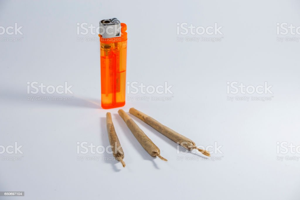 Joint of marijuana and a lighter on a white background. stock photo