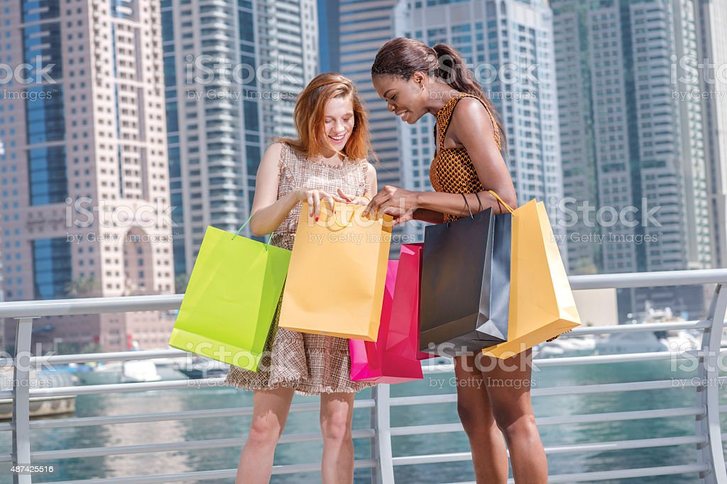 Joint purchases. Two girl friends in dresses holding shopping ba stock photo