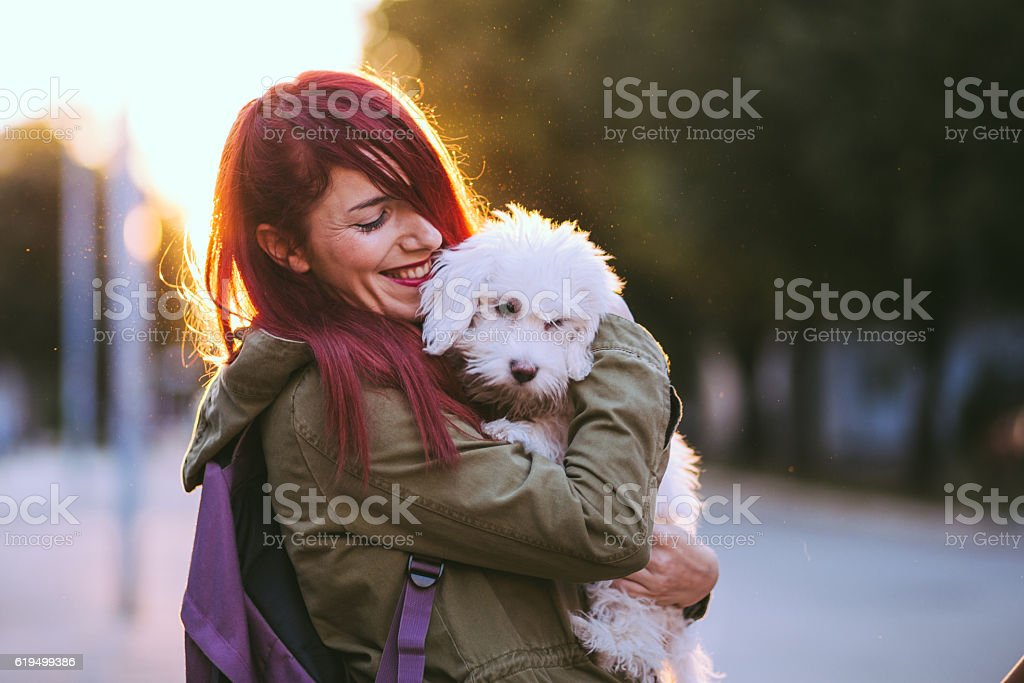 Jolly Girl Embracing Fluffy Puppy stock photo