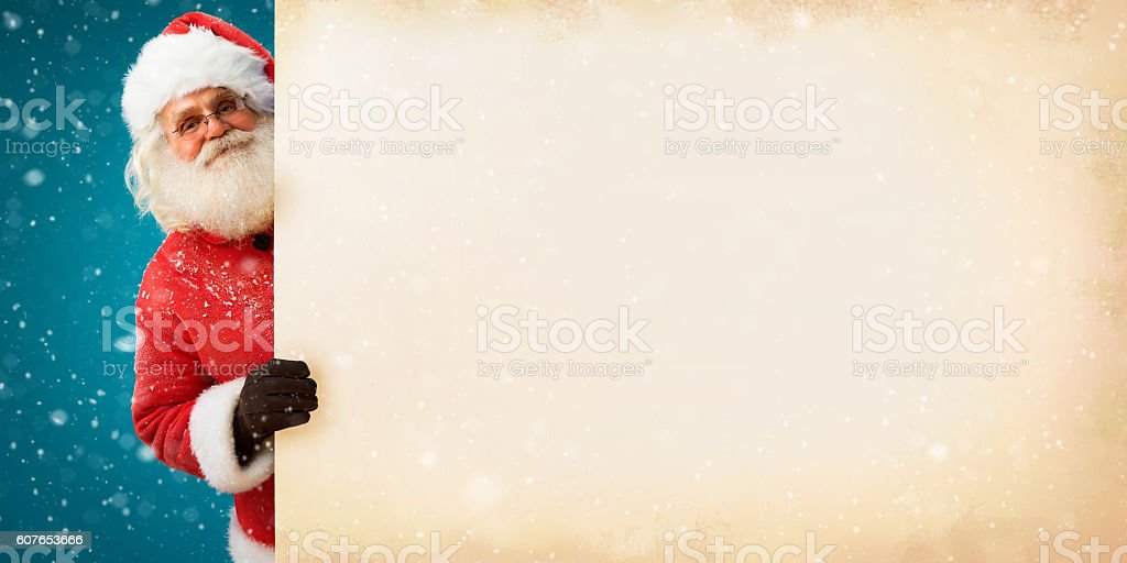 Jolly Santa Claus peeking out of an old paper banner stock photo