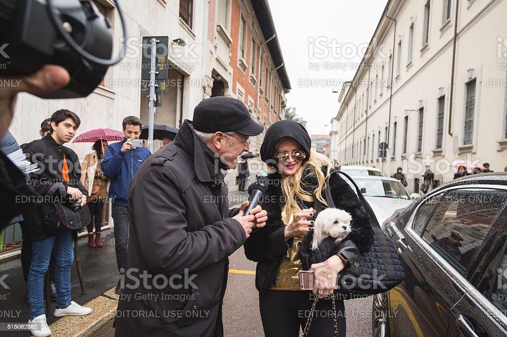 Jounnalist interviewing a woman outside Ermanno Scervino fashion stock photo