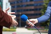 Journalist interviewing businessperson, corporate building in background