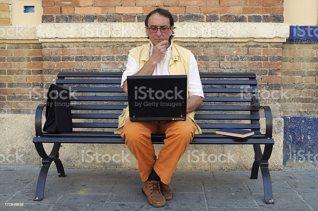 Journalist Using PC on a Bench.Urban Scene royalty-free stock photo