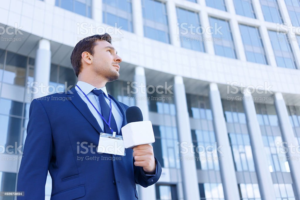 Journalist with microphone stands near the office stock photo