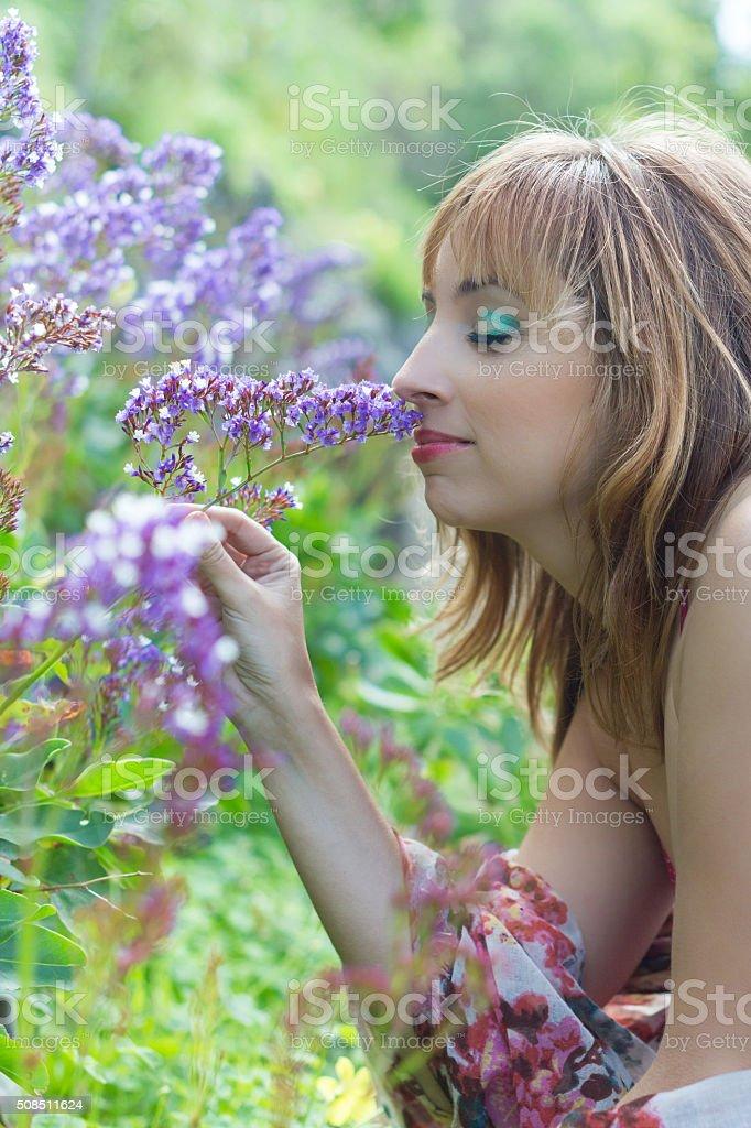Joven rubia en el campo oliendo flores violetas. stock photo