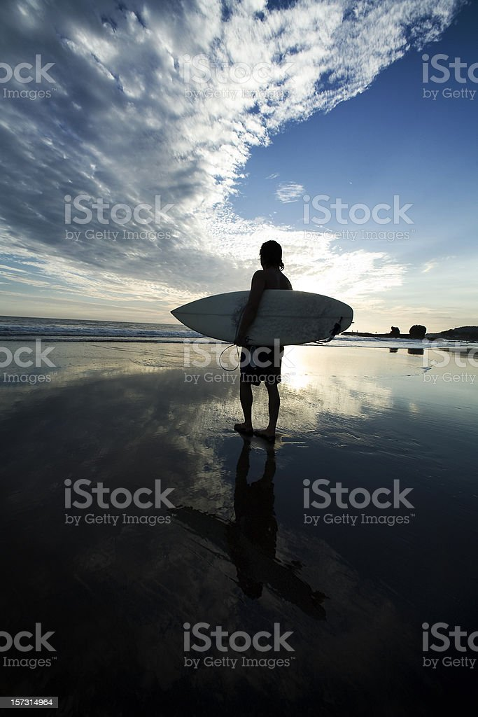 Joy being represented by a man with surfboard in sunset royalty-free stock photo