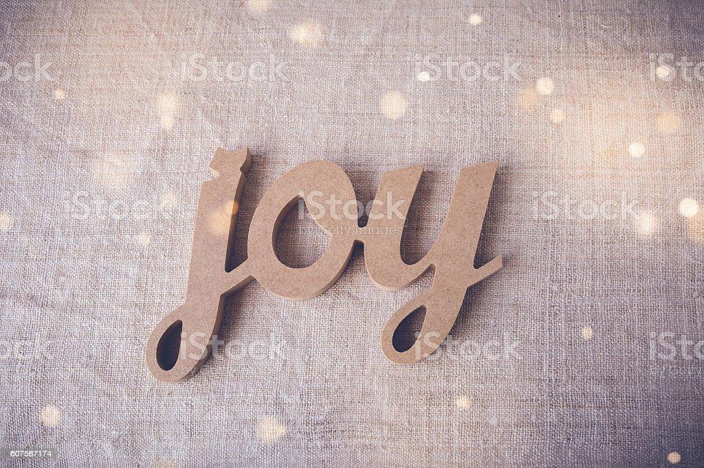 Joy word on fairy light toning background stock photo
