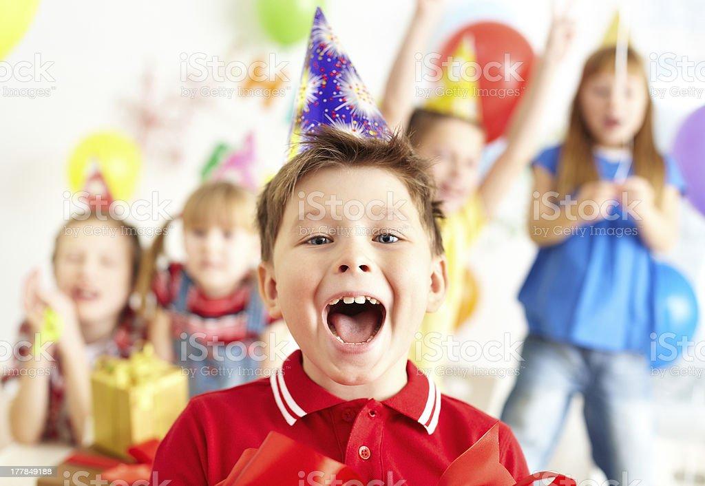 Joyful boy celebrating at a birthday party with other kids stock photo