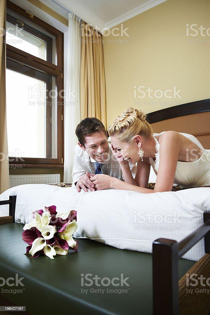 Joyful bride and groom in bedroom royalty-free stock photo