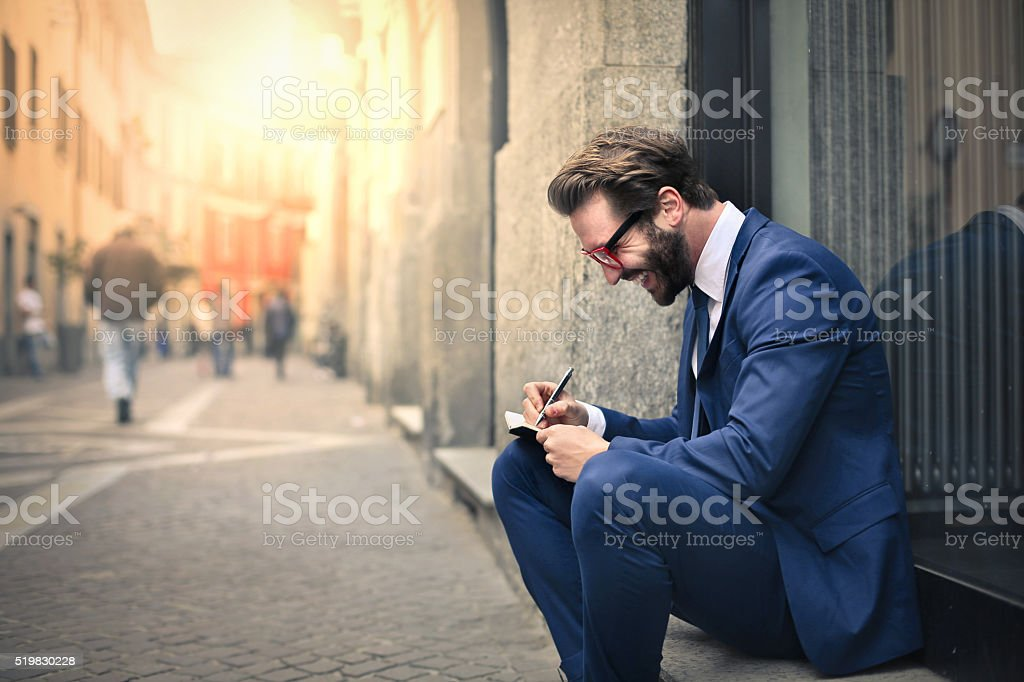 Joyful businessman writing in the street stock photo