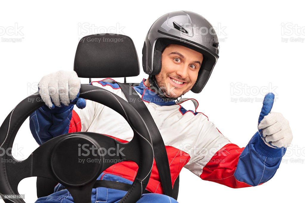 Joyful car racer giving a thumb up stock photo