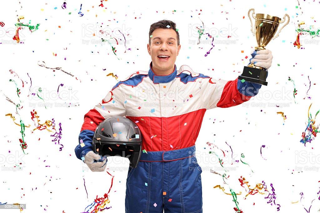 Joyful car racer holding a gold trophy stock photo