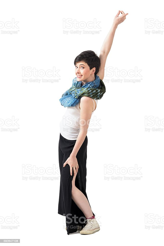 Joyful carefree woman spinning with raised arm looking at camera stock photo