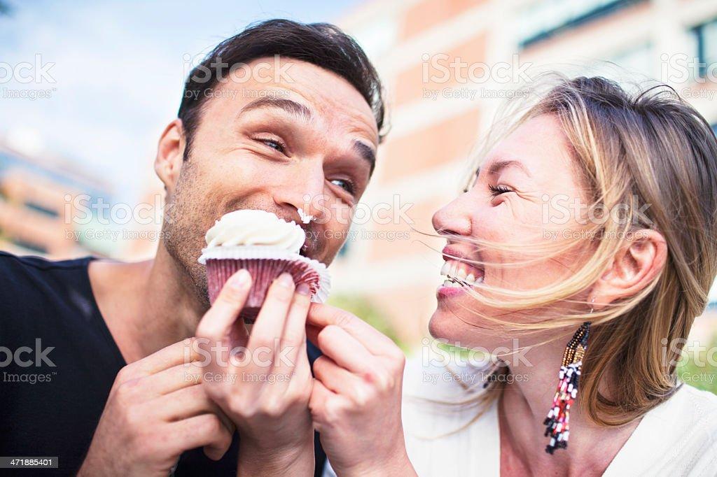 Joyful couple eating cupcake outdoors stock photo