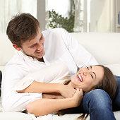 Joyful couple joking and laughing at home
