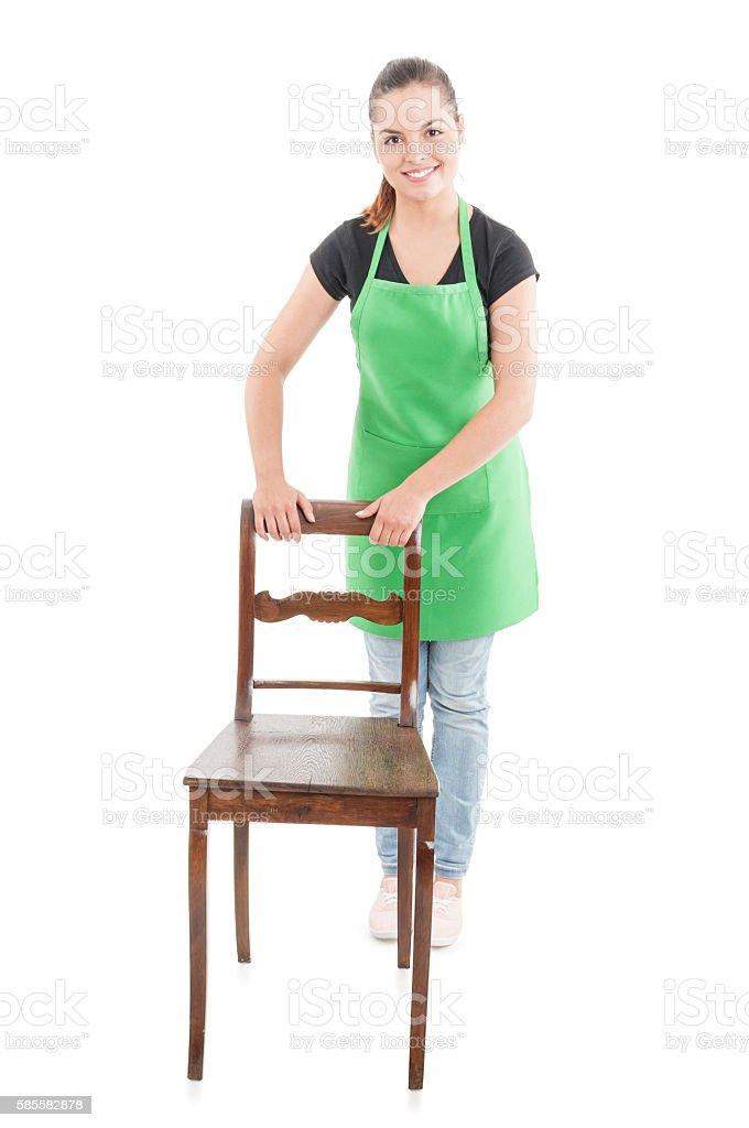 Joyful cute employee standing behind wooden chair stock photo