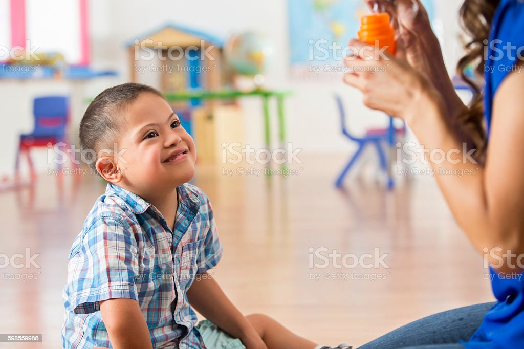 Joyful Down Syndrome boy playing with bubbles in learning center stock photo