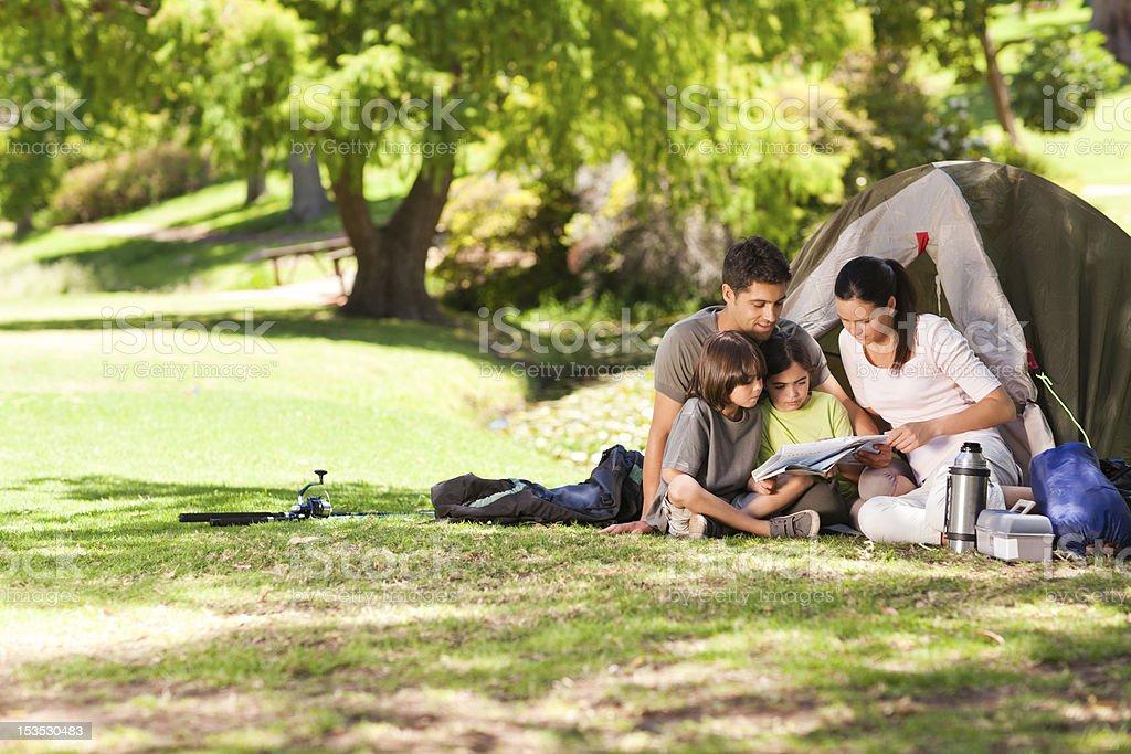 A joyful family camping and reading royalty-free stock photo