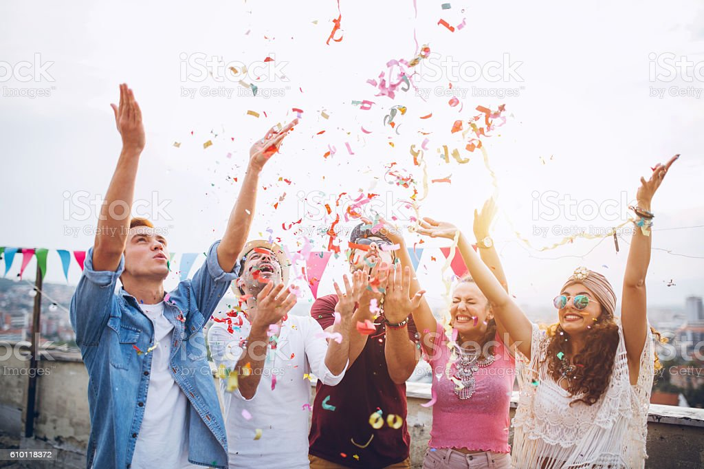 Joyful friends with confetti at the rooftop party stock photo