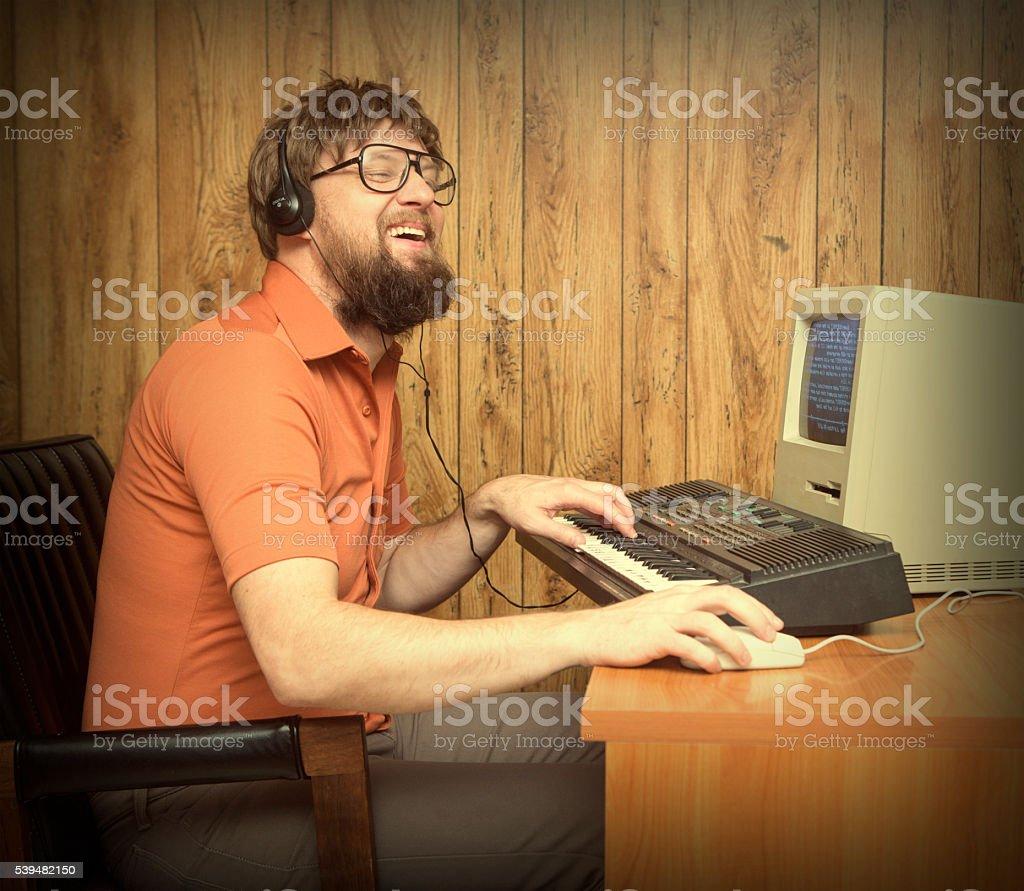 Joyful funny 1980s Nerd man recording synth music stock photo