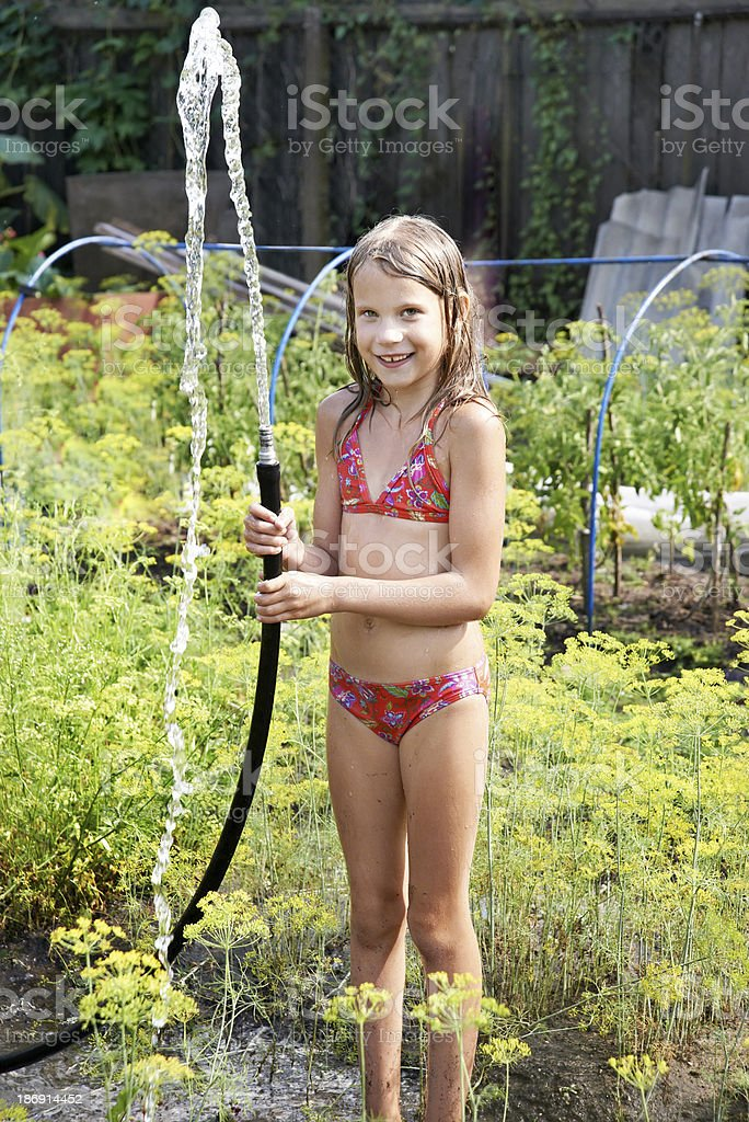 Joyful girl with garden hose and water royalty-free stock photo