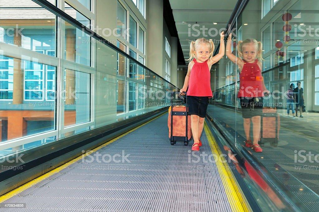 Joyful girl with her trunk on airport moving walkway stock photo