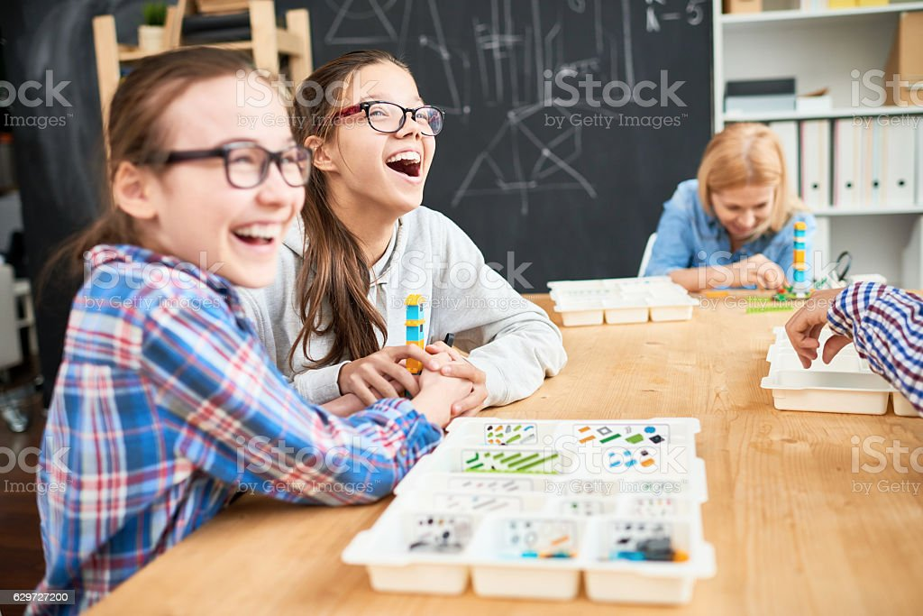 Joyful girls with building block tower stock photo