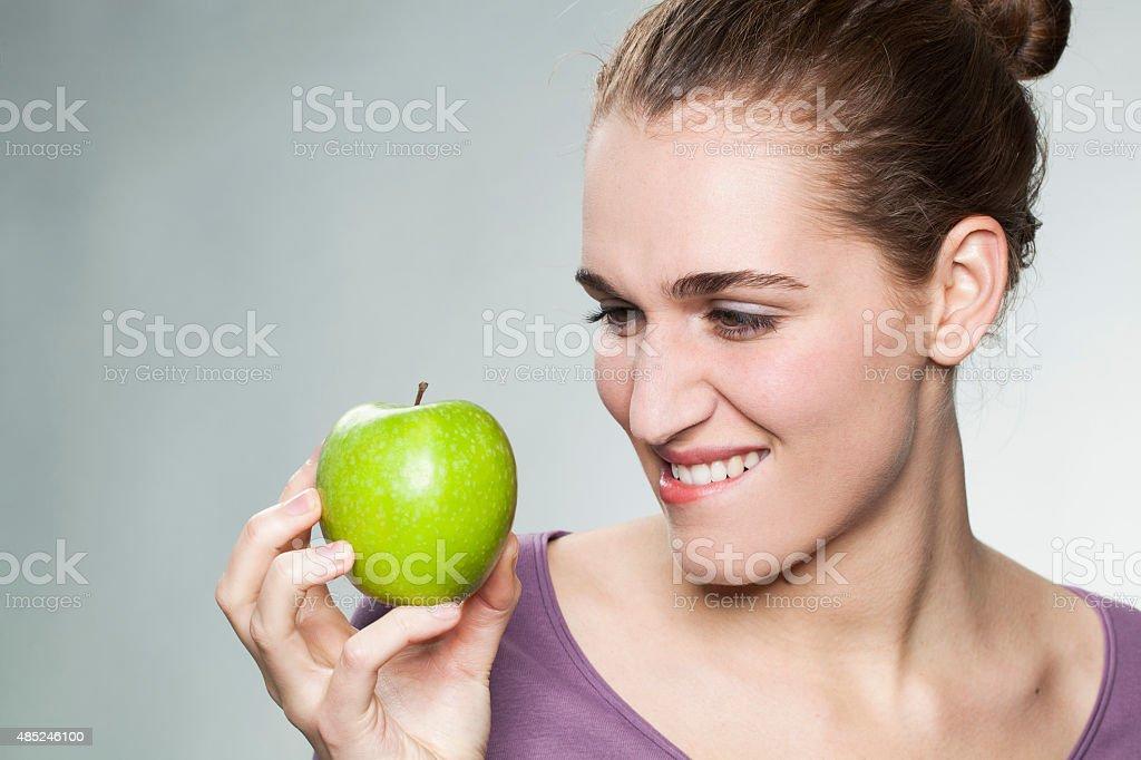 joyful gorgeous girl resisting in eating an apple stock photo
