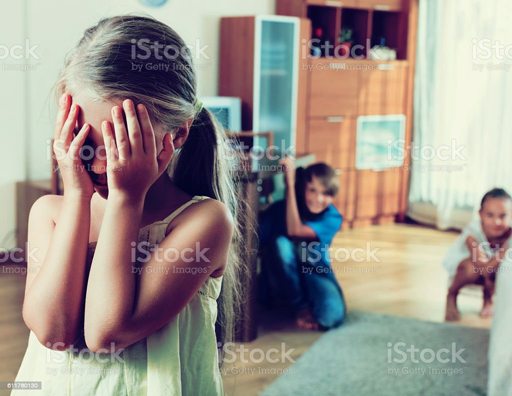 Joyful happy children hiding from girl stock photo