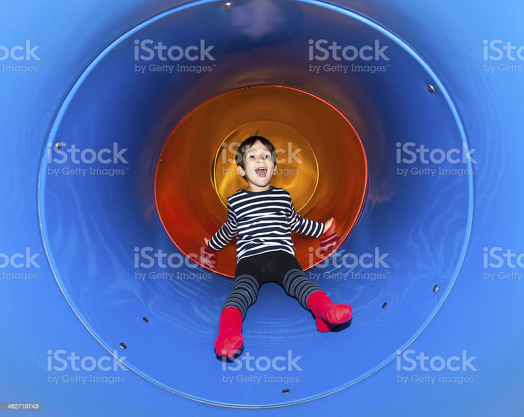 Joyful kid sliding in tube slide stock photo