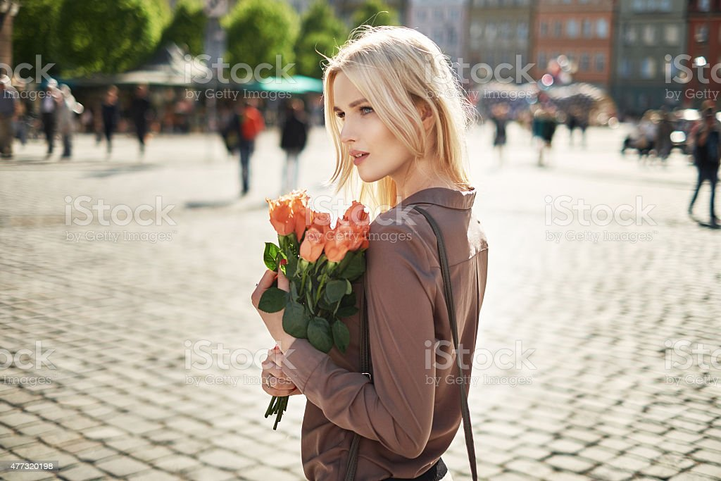 Joyful lady holding a bouquet of fresh roses stock photo