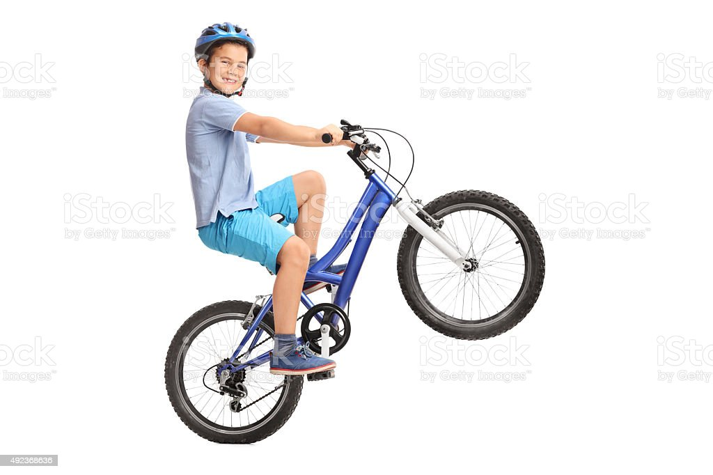 Joyful little boy performing a wheelie with his bike stock photo