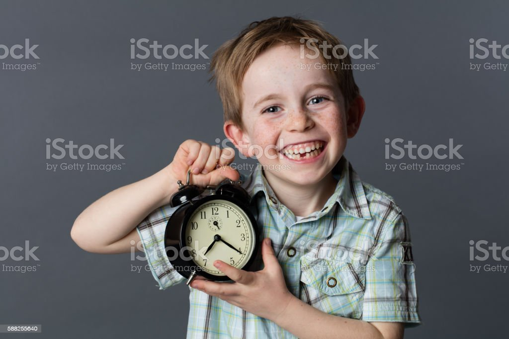 joyful little boy with missing tooth showing an alarm clock stock photo