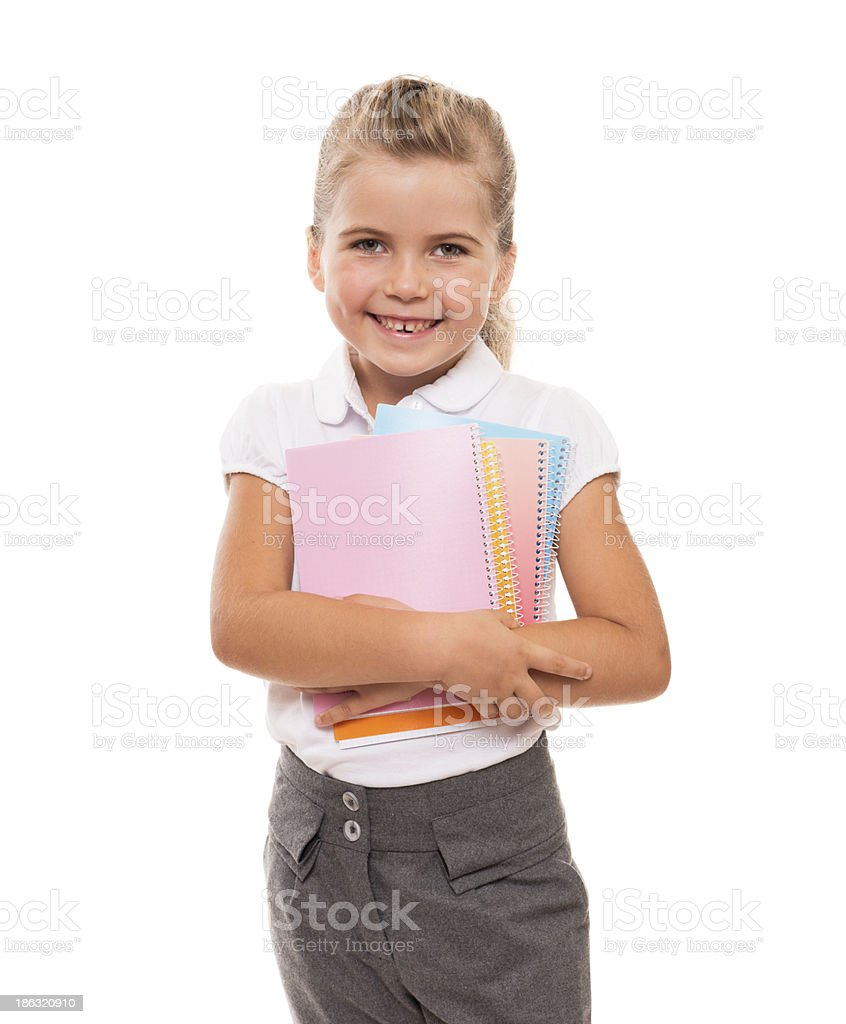 joyful little girl standing on white with few colorful notebooks royalty-free stock photo