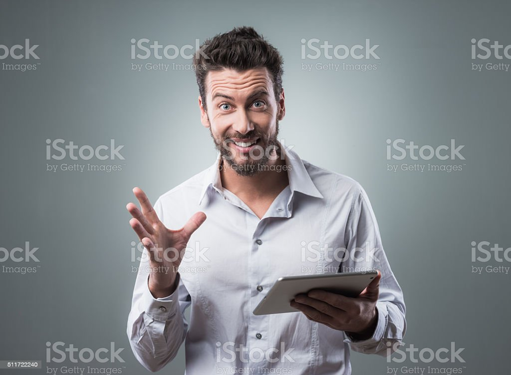 Joyful man using his tablet stock photo