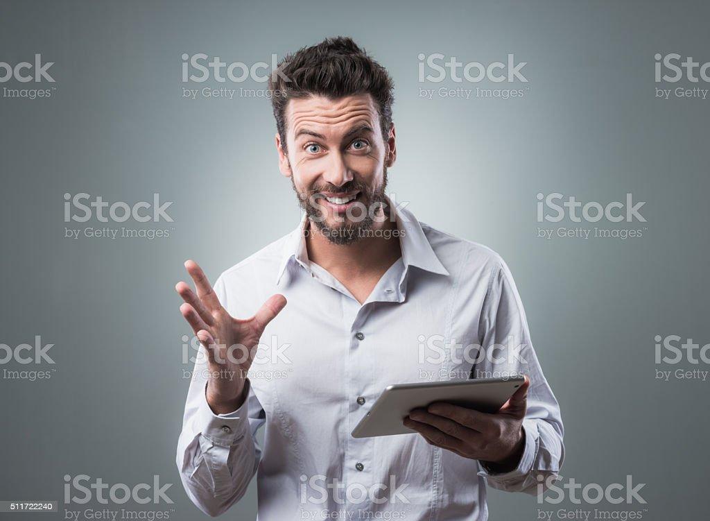 Joyful man using his tablet stock photo