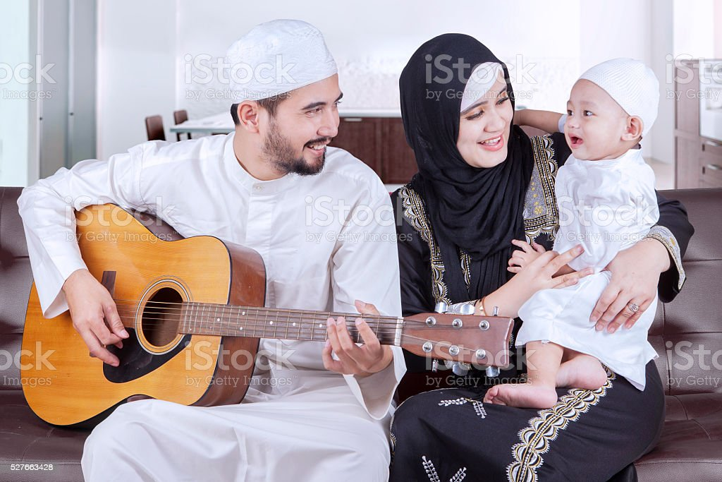 Joyful middle eastern family playing guitar stock photo