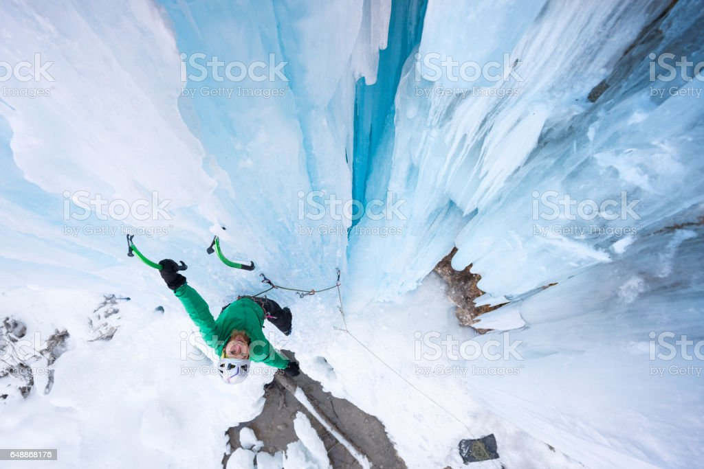 Joyful mountaineer holding on ice axe smiling at the camera stock photo