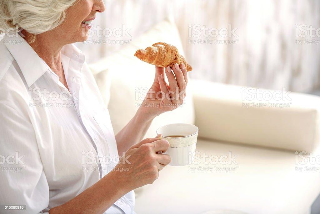 Joyful old lady eats croissant with hot beverage stock photo