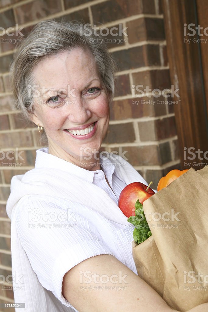 Joyful Senior Adult Coming Home with Bag of Groceries royalty-free stock photo