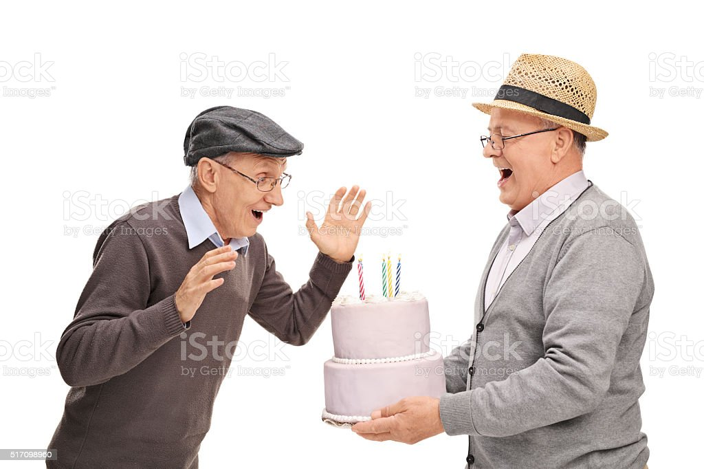 Joyful senior bringing cake to his friend stock photo