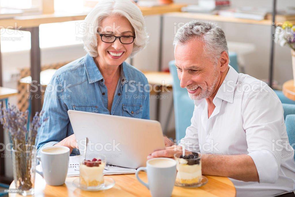 Joyful senior couple using laptop stock photo
