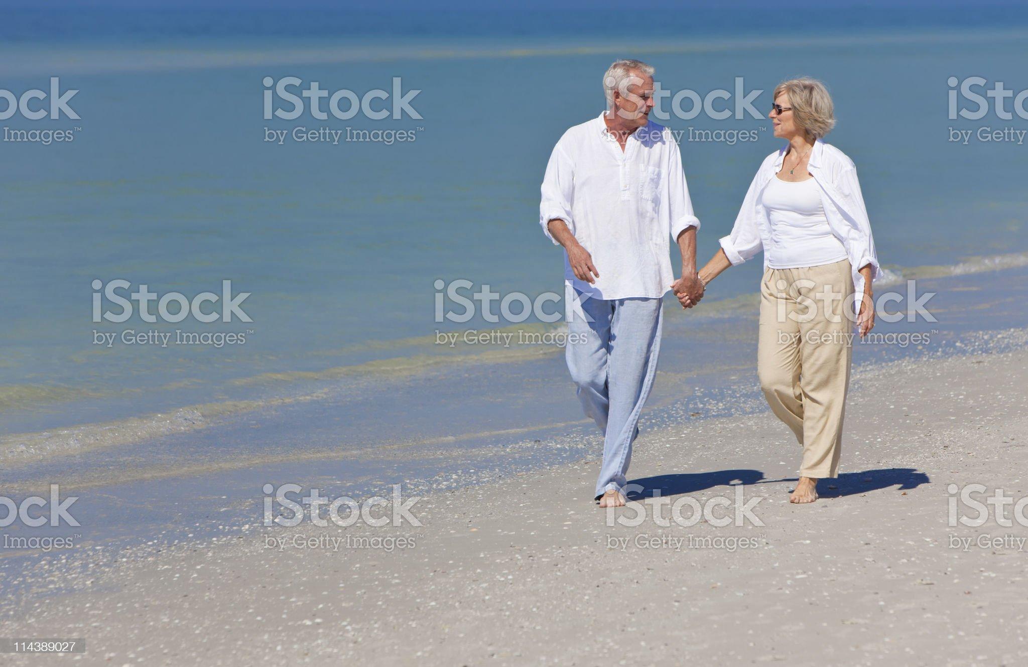 Joyful senior couple walking down beach hand in hand royalty-free stock photo