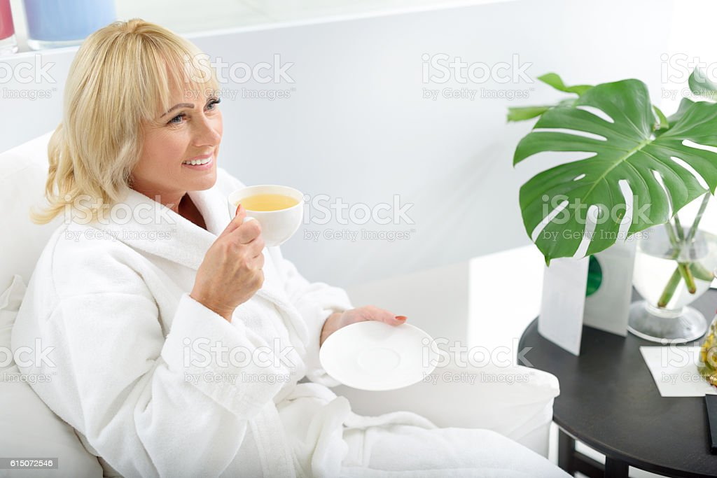 Joyful senior lady relaxing at spa stock photo