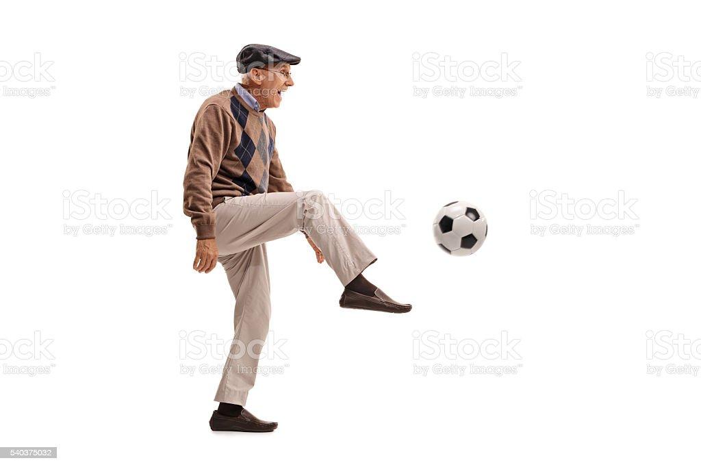 Joyful senior man kicking a football stock photo