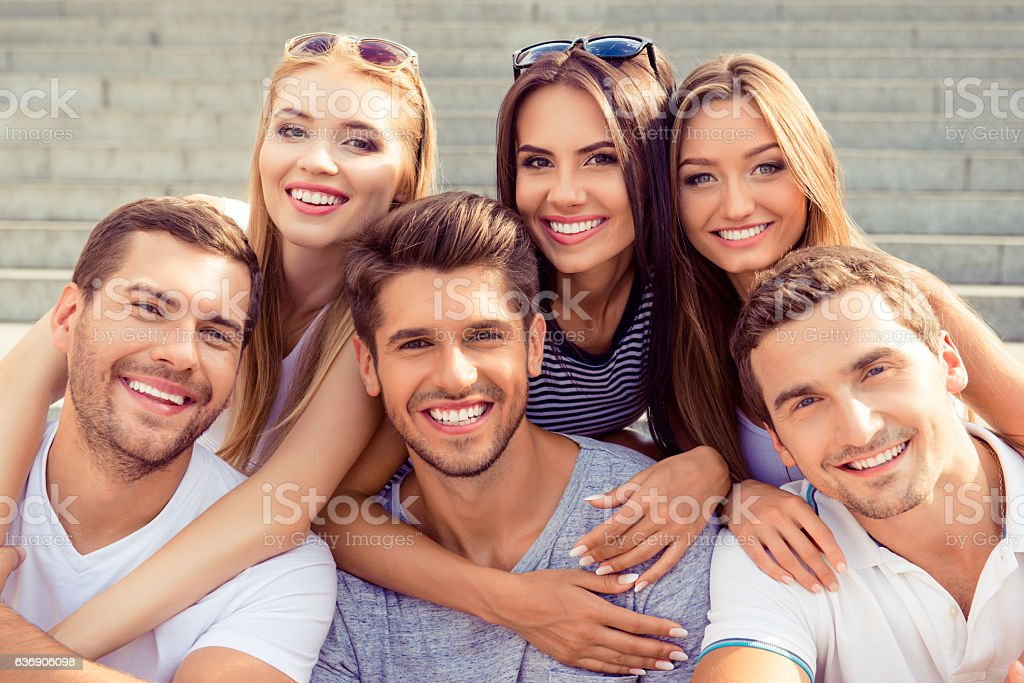 joyful  six friends embracing each other and having fun stock photo