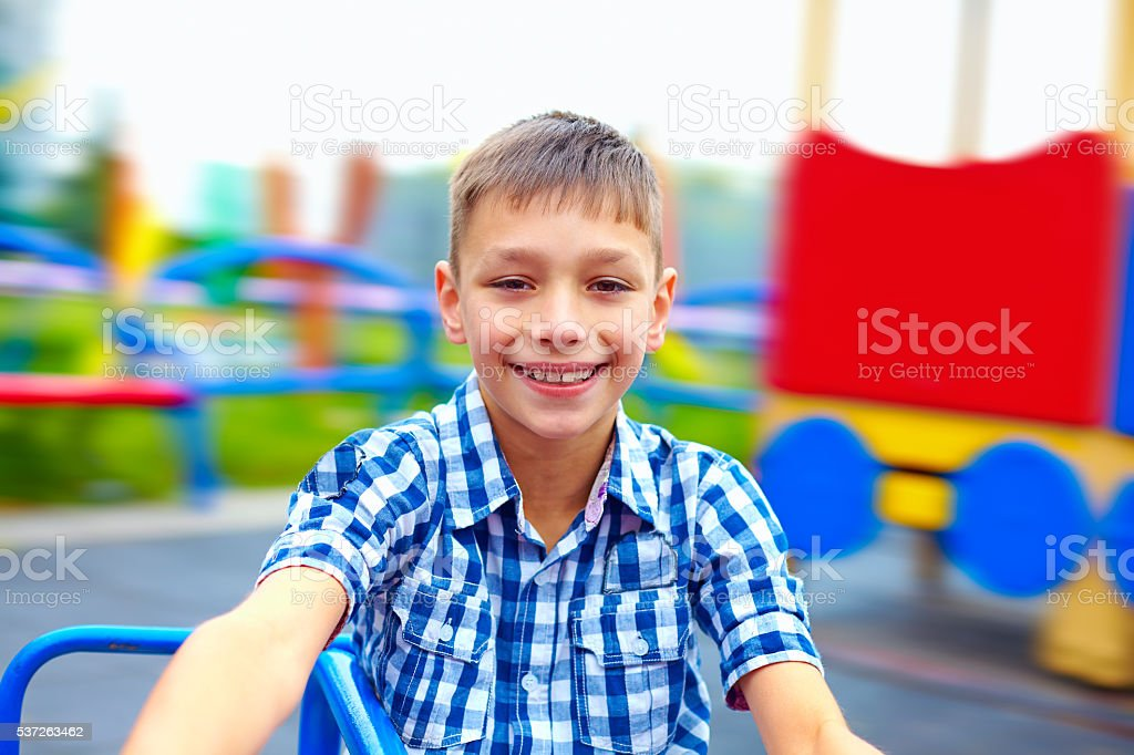 joyful teenage boy having fun on roundabout, playground stock photo