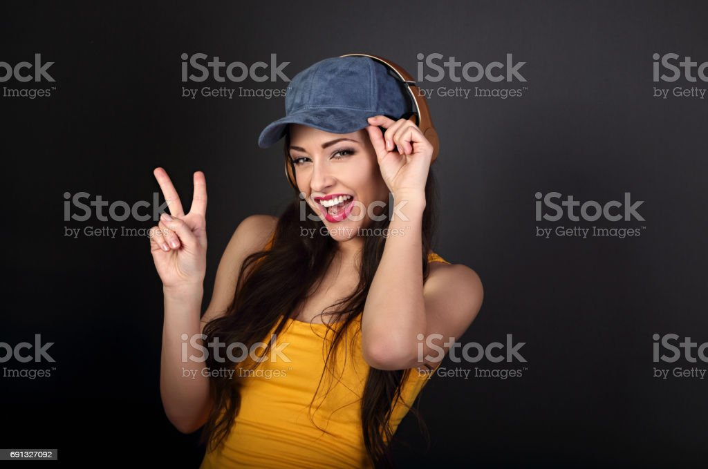 Joyful teenager listening the music in gold wireless headphone and showing victory v-sign gesture in yellow top and blue cap on dark grey background. stock photo