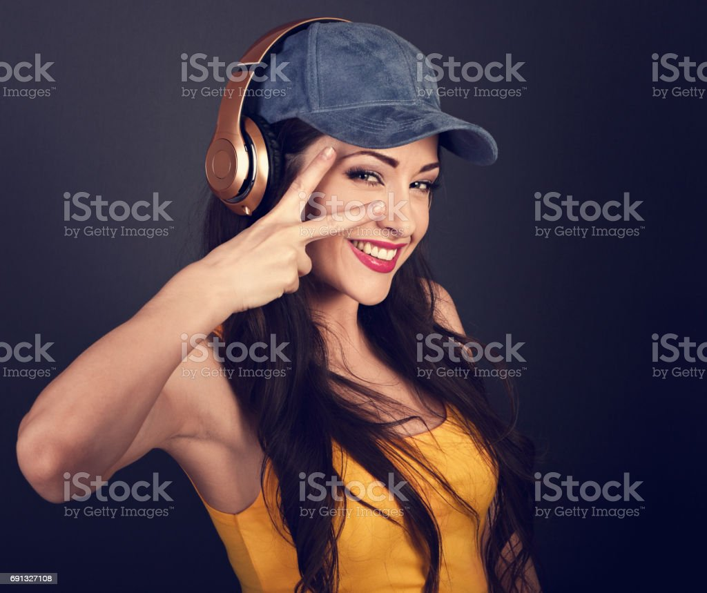 Joyful teenager listening the music in gold wireless headphone and showing victory v-sign gesture in yellow top and blue cap on dark grey background. Closeup toned portrait stock photo