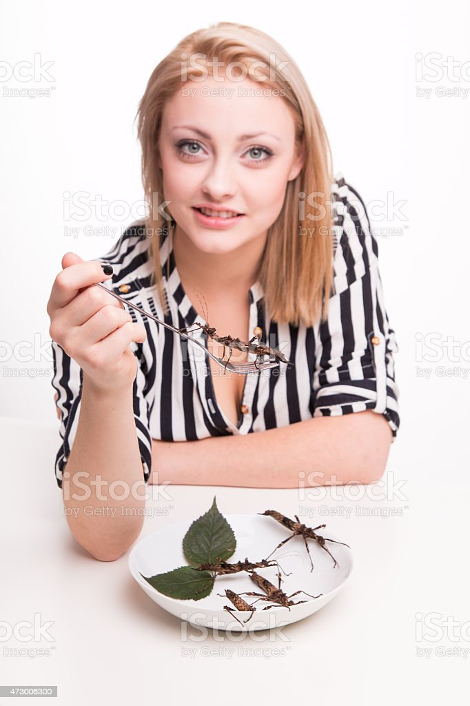 Joyful woman eating insects with a fork in a restaurant stock photo